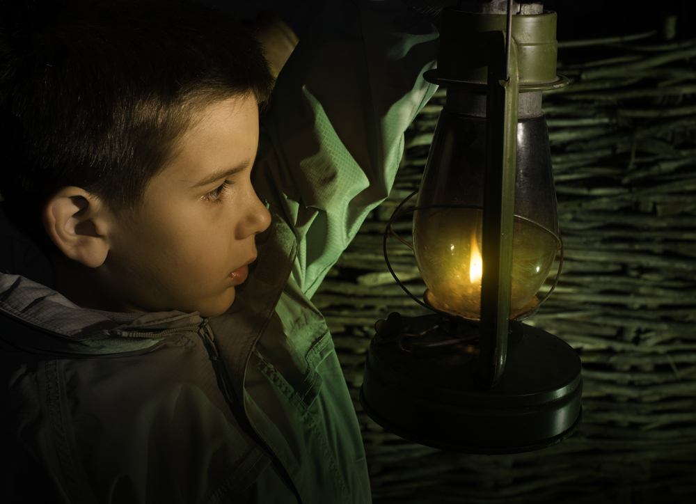 image of child in darkness with a lantern